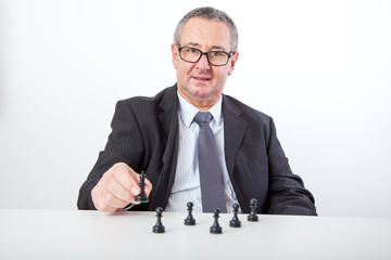 Man thinks strategically with chess pieces on the desk