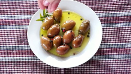Adding red and black pepper to green olives