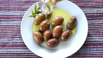 Adding oil to green olives