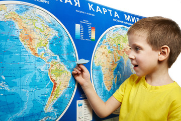 Little boy holding paper airplane on world map