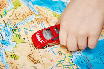 Child's hand with toy car on map of Africa