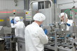 three workers in uniforms at production line in plant