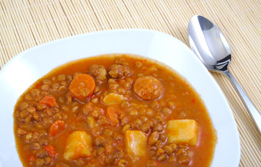 Brown cooked lentils with sausage, carrot and potato with metal