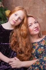 Мама и рыжеволосая дочка обнимаются у новогодней елки