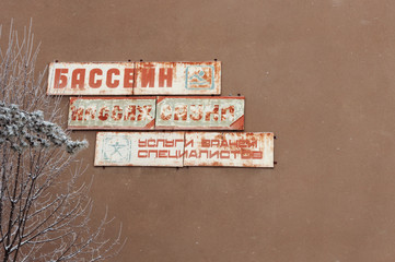 The old sign on the wall of a ruined house
