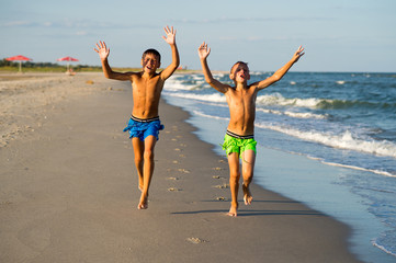Two happy boys running on the sea beach.