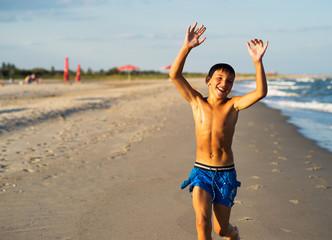 Happy boy running on the sea beach at summer.