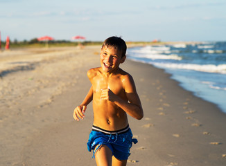 Happy boy running on the sea beach at summer.