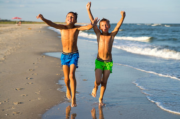 Two happy boys running on the sea beach at summer with raised ar