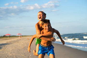 Happy kids playing on the beach on summer holidays.