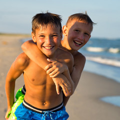 Closeup portrait of two happy teenagers playing on sea beach