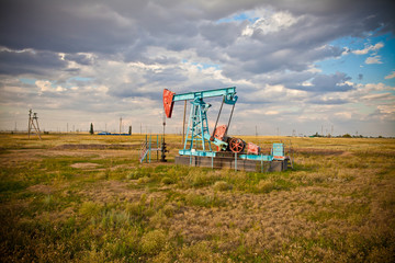 Oil pump in the field on a background cloudy sky
