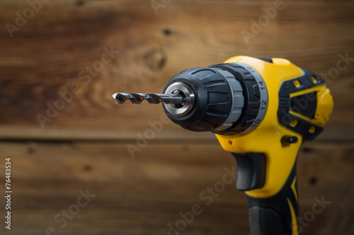 electric drill on a wooden background - 76483534