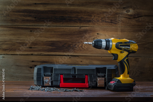 electric screwdriver on a wooden background - 76483545