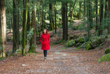 Young woman walking alone on a forest path