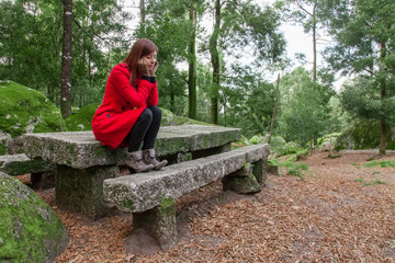 Young woman feeling depressed sitting on a stone table and bench