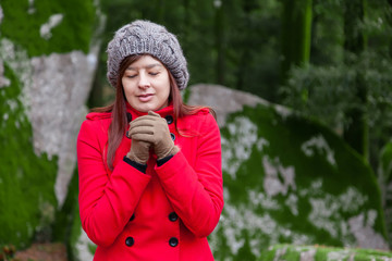 Young woman shivering with cold on a forest