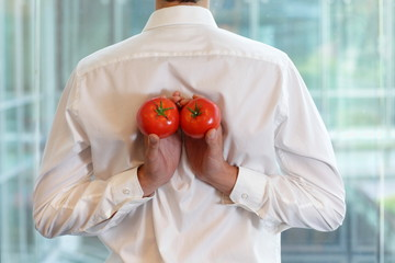 fit business man with tomatoes as a healhy snack - back view