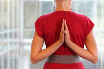Fit woman - namaste gesture on back - close up