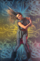 Beautiful woman dancer dancing over dark background with light r