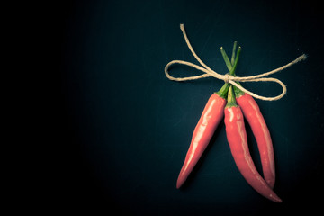 Three hot red chili pepper related by twine with on a black back