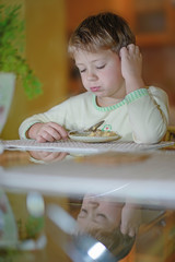 Boy eats at the table