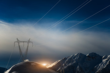 Pylons covered with snow in the high mountains carry energy down