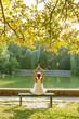 Caucasian woman practicing yoga at lake