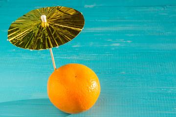 Mandarin under an umbrella on a blue background