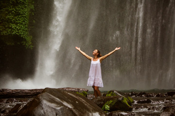 young woman doing yoga in a forest near waterfall