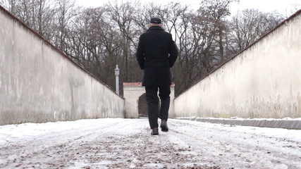 Man in black exiting area surrounded by massive walls