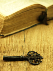 Key and old, open book with a damaged cover.