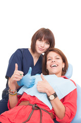 Female dentist and patient showing thumbs-up