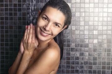 Attraktive Frau steht in der Dusche und lächelt