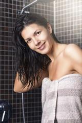 Frau mit feuchten Haaren steht in der Dusche