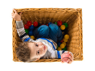 Cute kid inside basket playing with colored balls