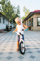 Adorable little blond boy with bicycle outdoors.
