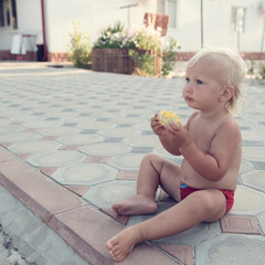 Little cute boy with blue eyes eating corn.