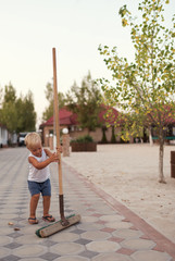 Portrait of  little blond boy with broom in his hand outdoors