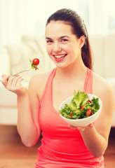 smiling teenage girl with green salad at home