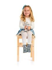 Little blonde girl sitting on chair
