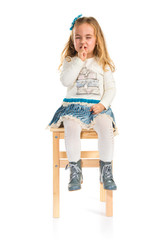 Little blonde girl sitting on chair making silence gesture