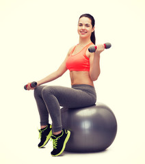 teenager with dumbbells sitting on fitness ball