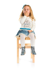 Surprised little blonde girl sitting on chair