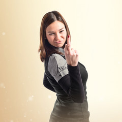 young girl making horn gesture over white background