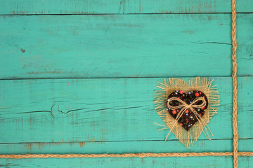 Burlap and fabric heart on teal blue wood background