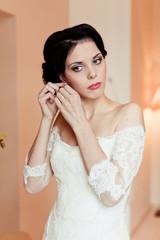 Gorgeous bride on her wedding day, wear earrings, morning bride
