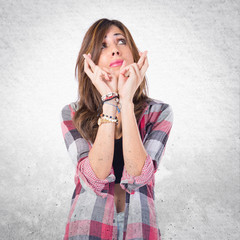Girl with her fingers crossing over white background