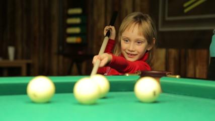 Little girl plays billiards
