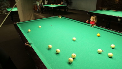 Little girl with mom  plays billiards